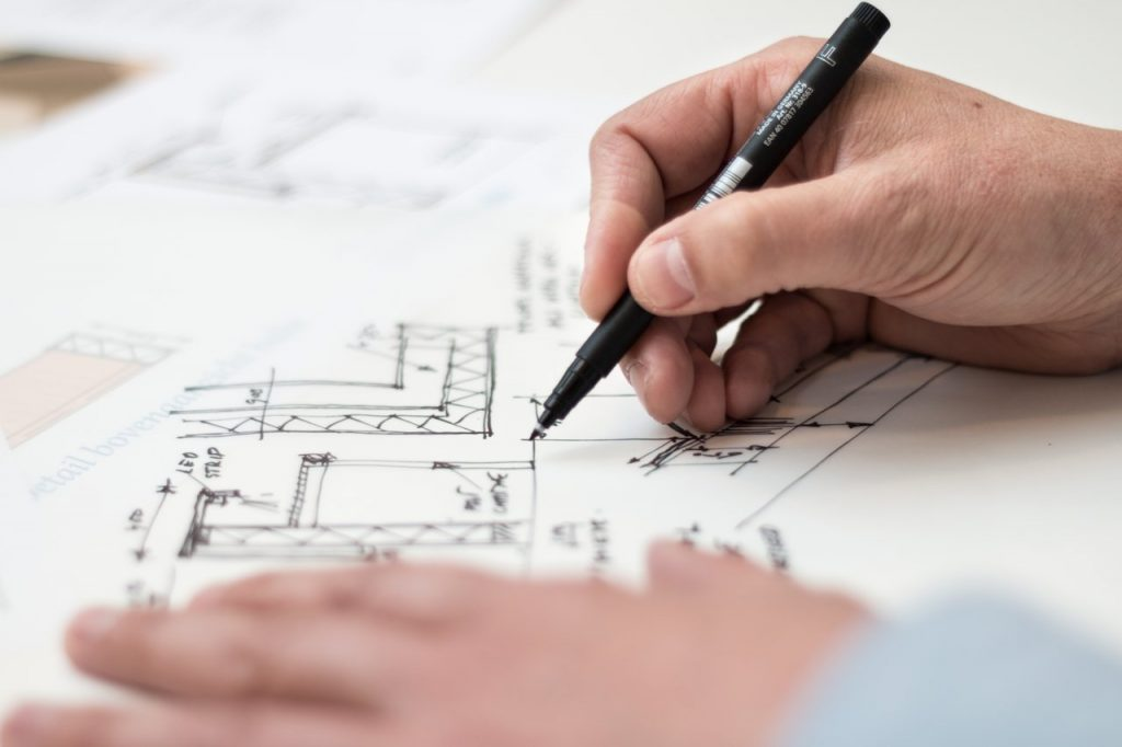 A hand holding pen over the electrical design on paper